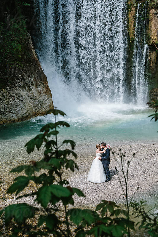 kissing bride and groom at a waterfall from above by Leander Nardin for Stocksy United