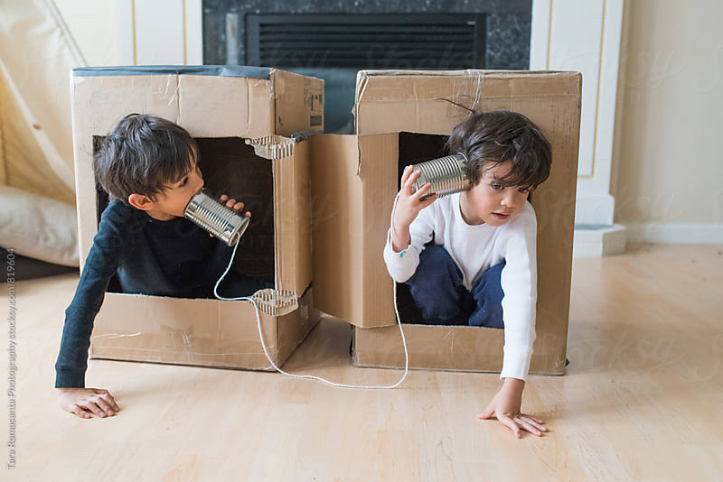 two children playing in boxes talking over a tin can telephone by Tara Romasanta for Stocksy United