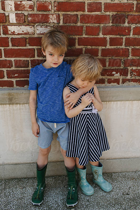 Boy puts his arm protectively around his little sister. by Julia Forsman for Stocksy United