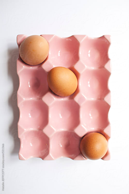 3 eggs sitting in a pink ceramic carton by Natalie JEFFCOTT for Stocksy United
