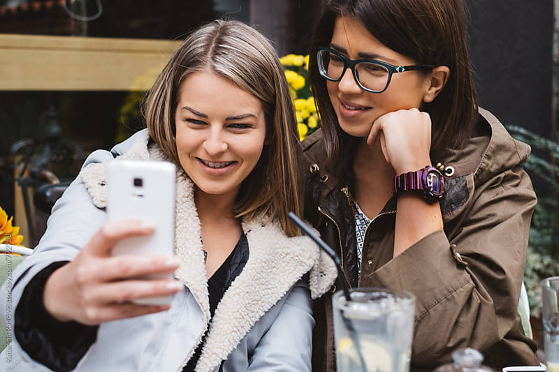 Two Girlfriends Taking Selfies While Sitting in a Cafe by Katarina Radovic for Stocksy United