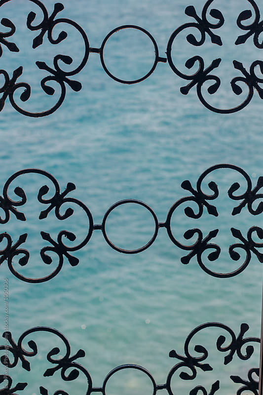 Close up look to the sea through the ornament window  by Branislava Živić for Stocksy United