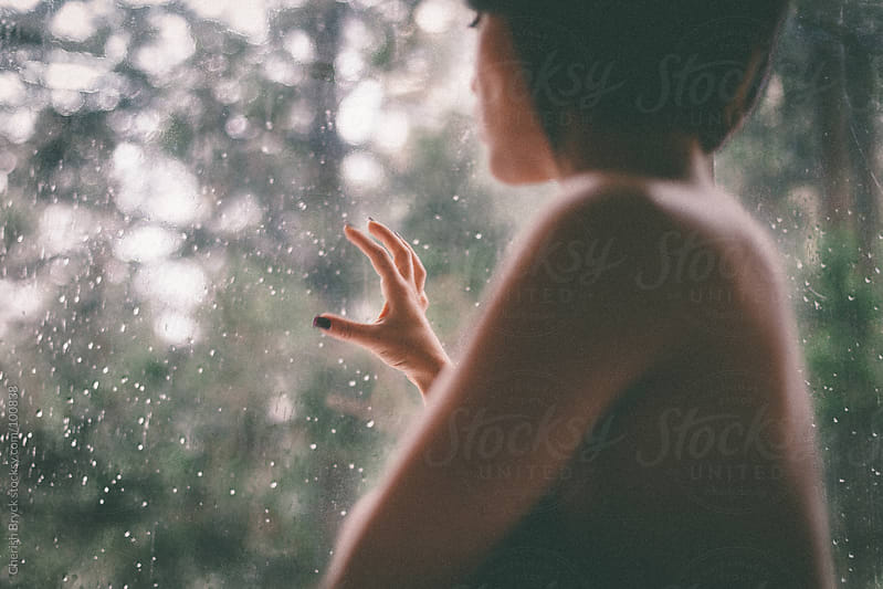 Woman views forest through the window. by Cherish Bryck for Stocksy United