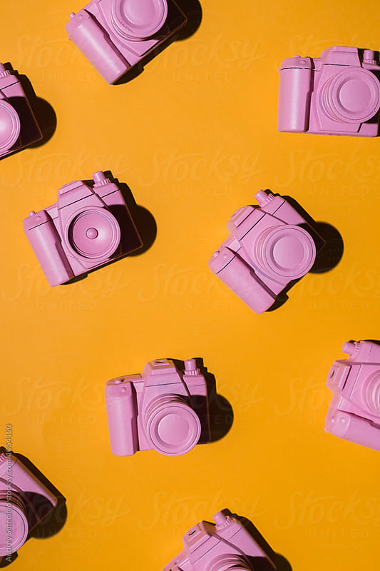 Pink cameras arranged on orange/yellow background. by Audrey Shtecinjo for Stocksy United