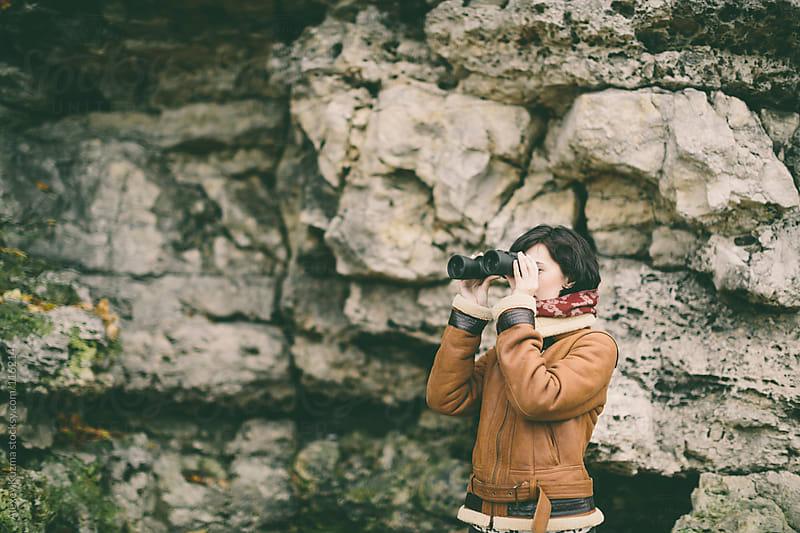 Woman looking with binoculars by Alexey Kuzma for Stocksy United