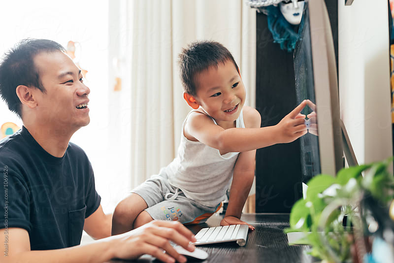Father and son using computer at home by Maa Hoo for Stocksy United