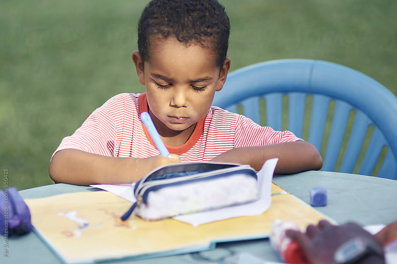 Boy is doing homework in the garden by Per Swantesson for Stocksy United