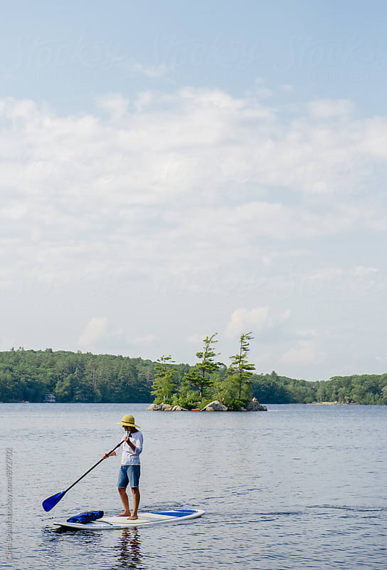 Woman paddleboarding on a lake in summer by Cara Slifka for Stocksy United