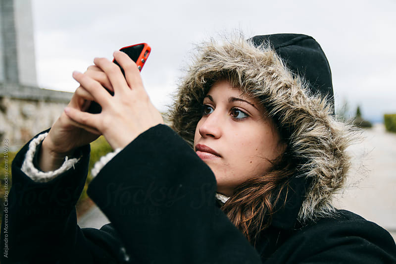 Young woman wearing parka coat and hood taking a picture with her cellphone by Alejandro Moreno de Carlos for Stocksy United