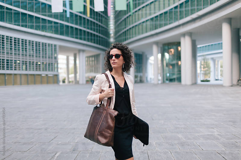 Businesswoman walking in the business district by Davide Illini for Stocksy United