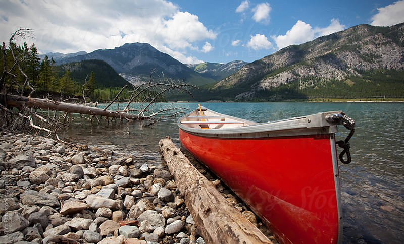 Red canoe on a mountain lake in Alberta, Canada by Mima Foto for Stocksy United