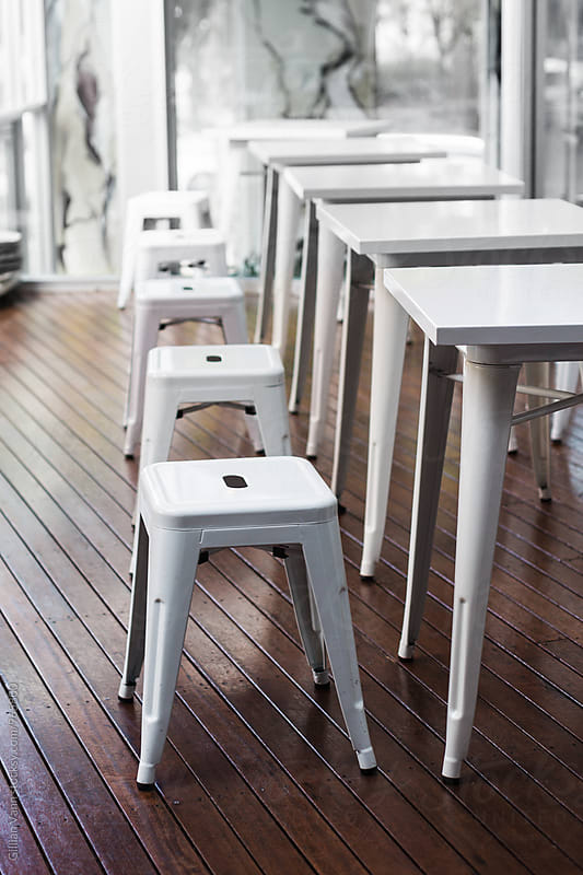 metal stools and white tables in a cafe by Gillian Vann for Stocksy United