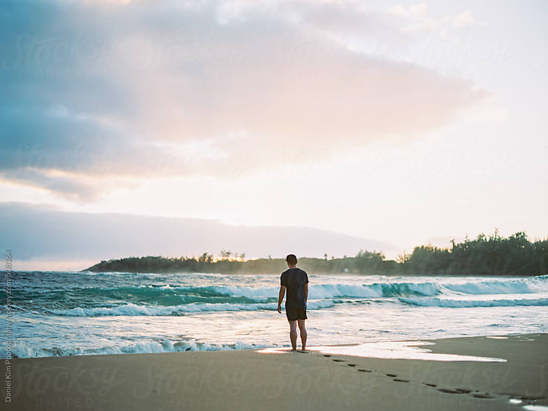 Man walking on beach at sunrise by Daniel Kim Photography for Stocksy United