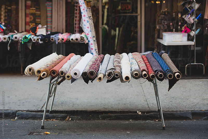 Rows of fabric for sale in the street by Lauren Naefe for Stocksy United