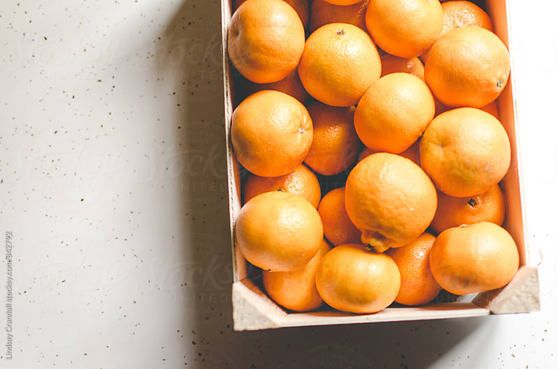 Small oranges in box by Lindsay Crandall for Stocksy United