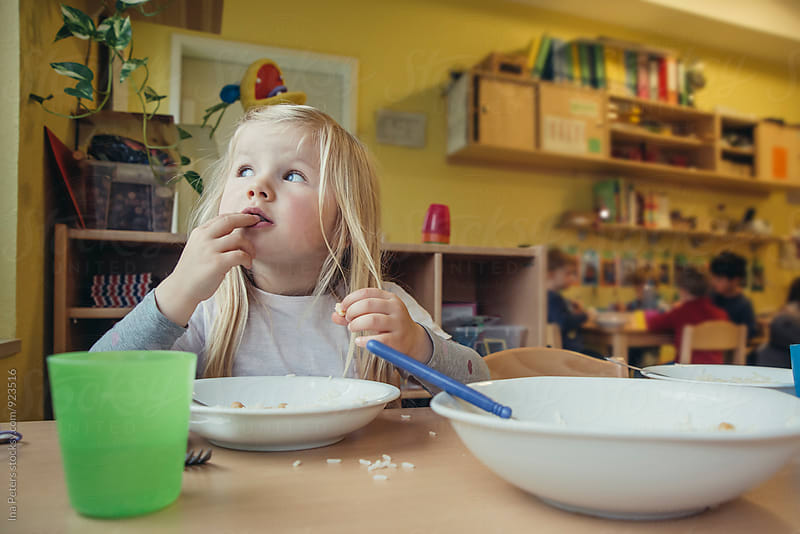 People: Girl eating lunch in Kindergarden by Ina Peters for Stocksy United