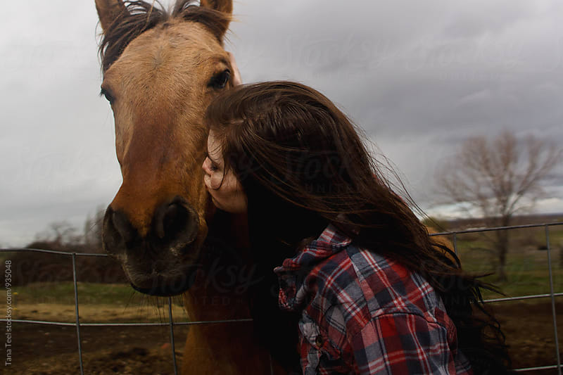 young woman kisses horse on muzzle by Tana Teel for Stocksy United