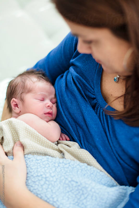 Mother Holding Sleeping Newborn Son by Holly Clark for Stocksy United