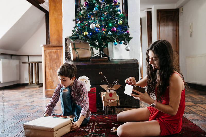 Girl and her brother opening their Christmas present on boxing day by Beatrix Boros for Stocksy United