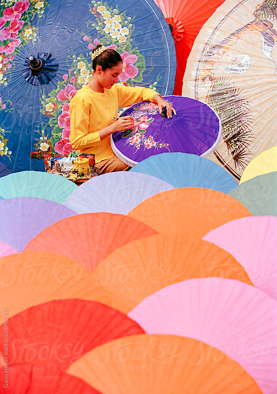 Woman painting umbrellas, Bo Sang umbrella village, Chiang Mai,  by Gavin Hellier for Stocksy United