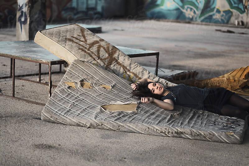 Pretty brunette girl lying on torn mattress by Sanja (Lydia) Kulusic for Stocksy United