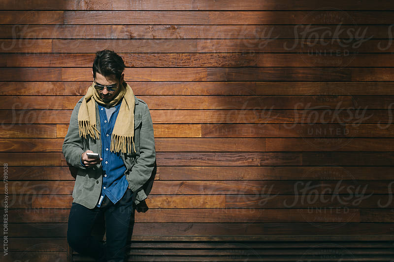 Young Man Using a Mobile Phone Outdoor by VICTOR TORRES for Stocksy United
