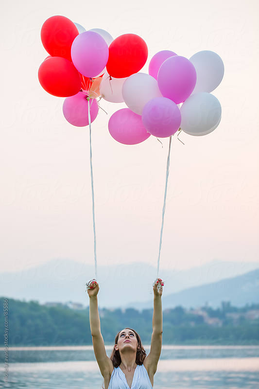 Young woman with balloons by michela ravasio for Stocksy United