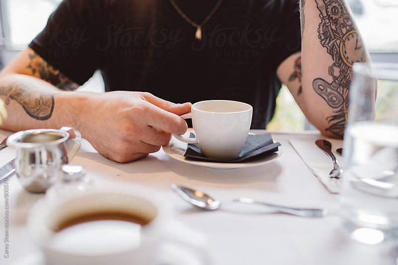 Young man with tattoos drinking coffee by Carey Shaw for Stocksy United
