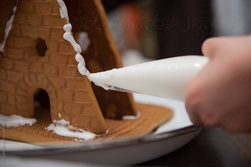 A child squeezes frosting onto a gingerbread house by Cara Dolan for Stocksy United