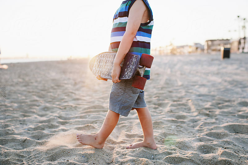 Body of a young boy holding a skateboard in the beach sand by Kristin Rogers Photography for Stocksy United