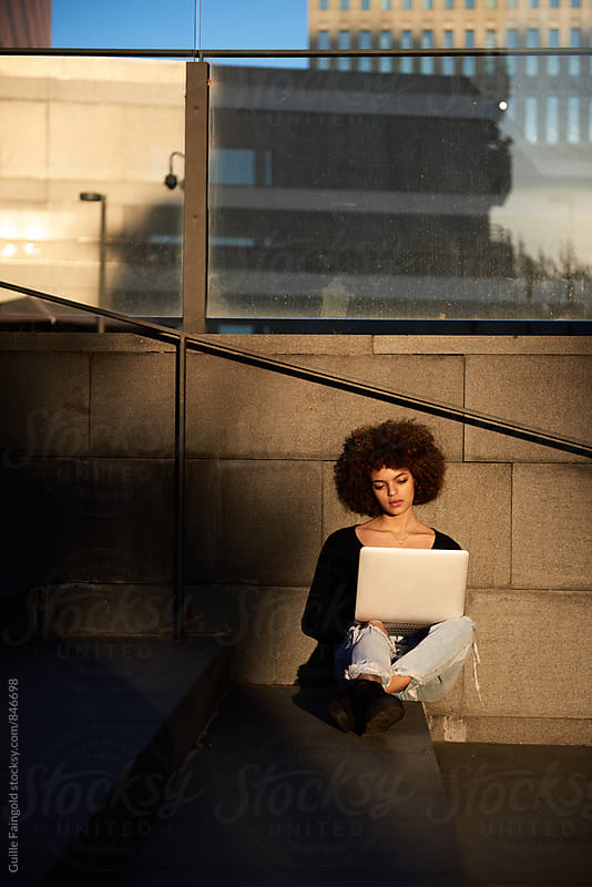 Young woman with afro using her laptop by Guille Faingold for Stocksy United