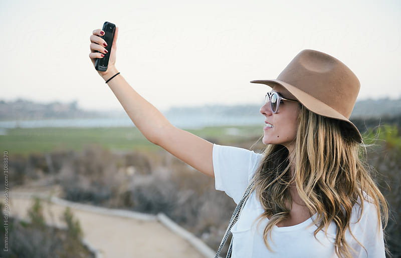 Woman holding up her smartphone to take a selfie shot by Emmanuel Hidalgo for Stocksy United