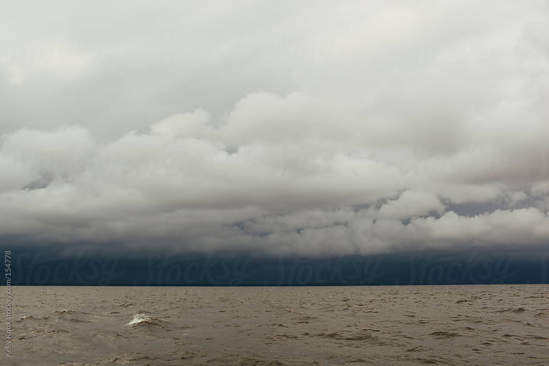 summer storm brewing across water by Kelly Knox for Stocksy United