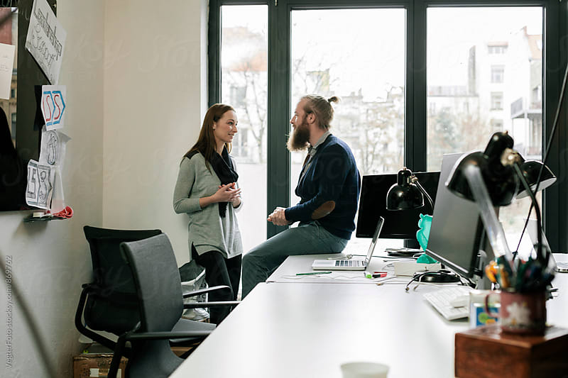Man and Woman talking at Desk by VegterFoto for Stocksy United