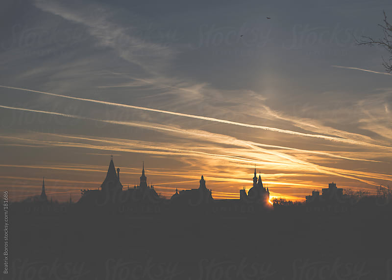 Silhouette of a castle's rooftops in the city at Sunrise by Beatrix Boros for Stocksy United