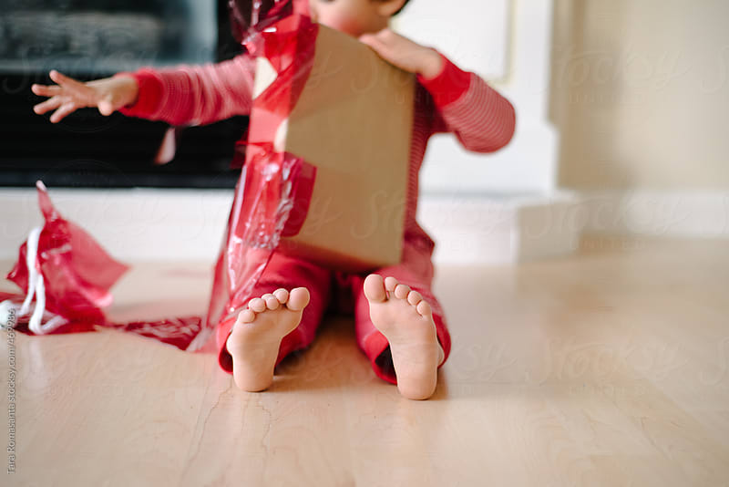 child unwraps a Christmas present by Tara Romasanta for Stocksy United