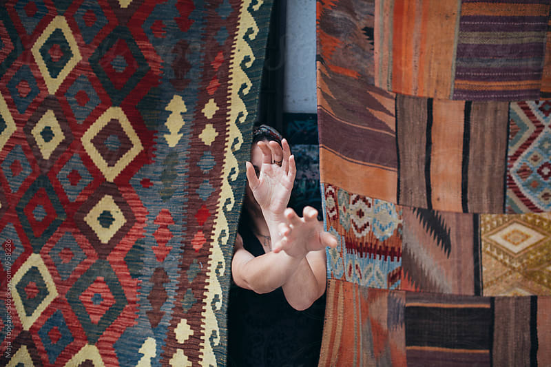 Woman covering her face with hands in front of a colorful patchwork by Maja Topcagic for Stocksy United