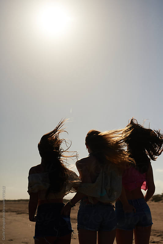 Three girlfriends walking from camera along beach by Guille Faingold for Stocksy United