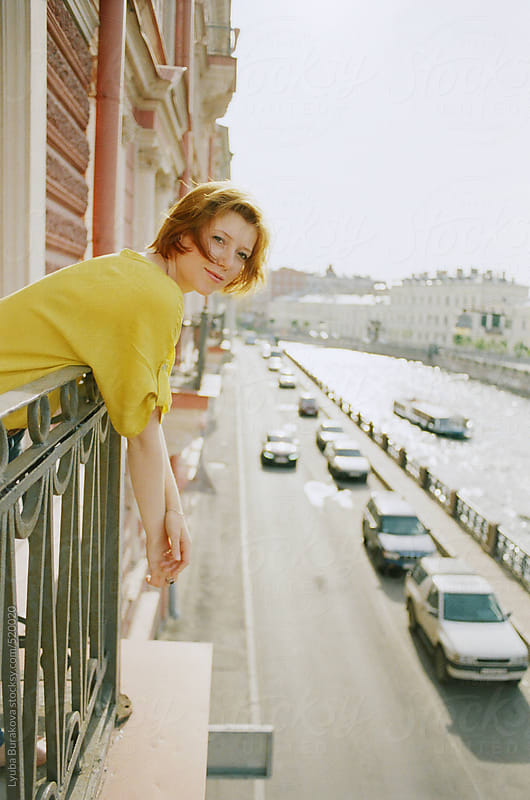 Young woman hanging from the balcony and looking at camera by Lyuba Burakova for Stocksy United