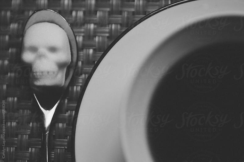 Black coffee with a sugar cube in the shape of a skull on a spoon  by Carolyn Lagattuta for Stocksy United
