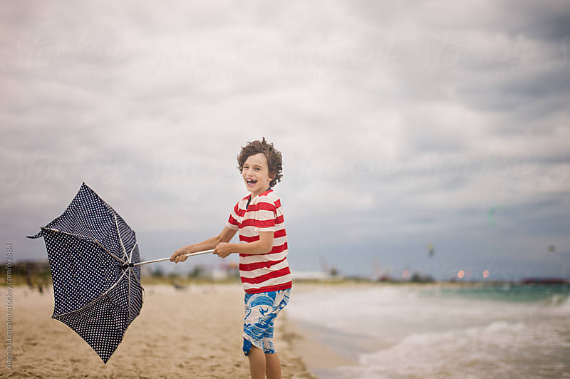 Boy smiling and struggling with an umbrella at the beach by Angela Lumsden for Stocksy United
