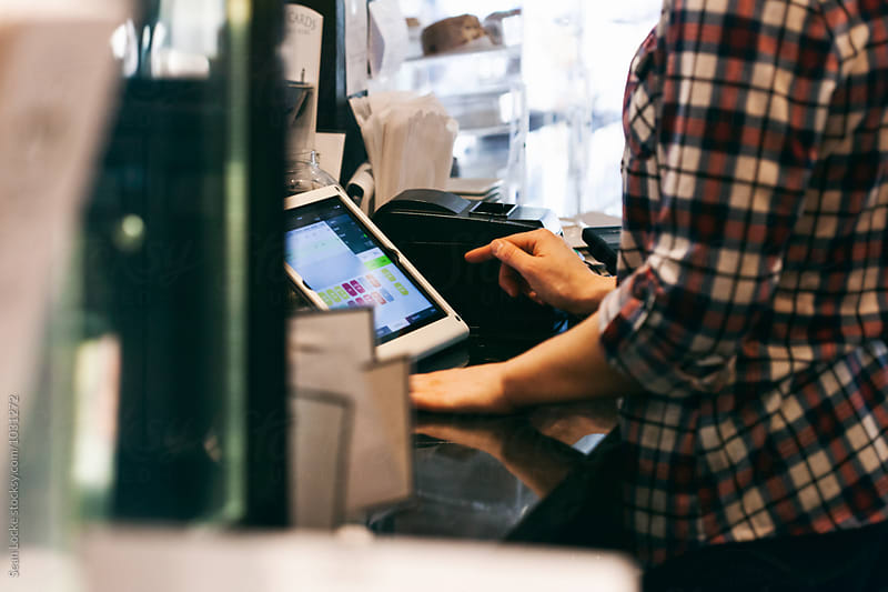 Bakery: Barista Uses Digital Tablet Cash Register by Sean Locke for Stocksy United