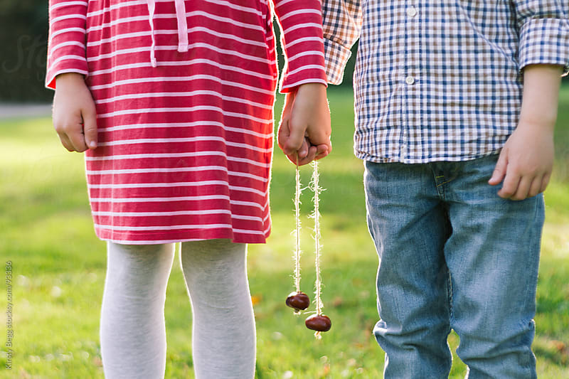 Boy and Girl holding hands with conkers by Kirsty Begg for Stocksy United