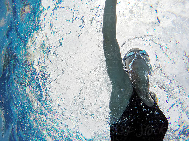 Woman swimming in a pool by ACALU Studio for Stocksy United