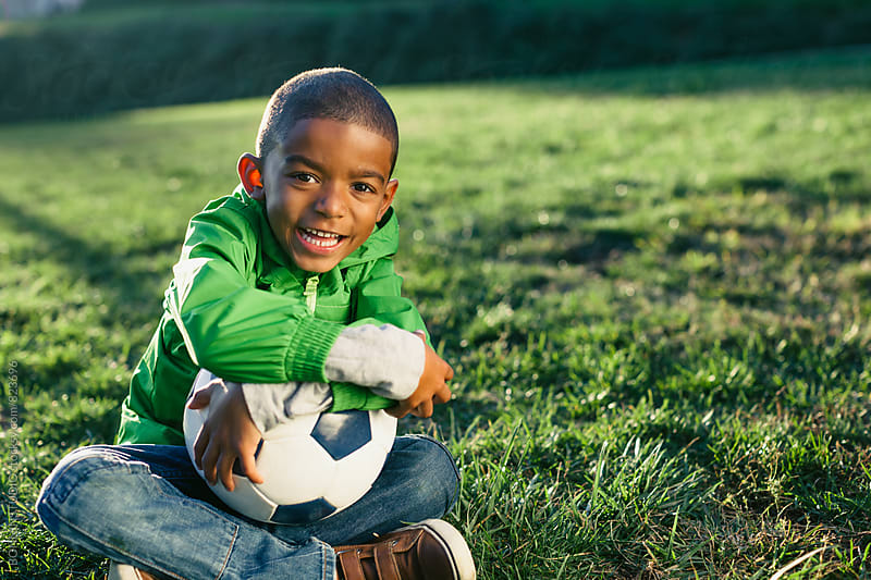 Portrait of a kid laughing holding a soccer ball outside. by BONNINSTUDIO for Stocksy United
