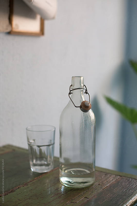 Old water bottle and glass on wood table by Lydia Cazorla for Stocksy United