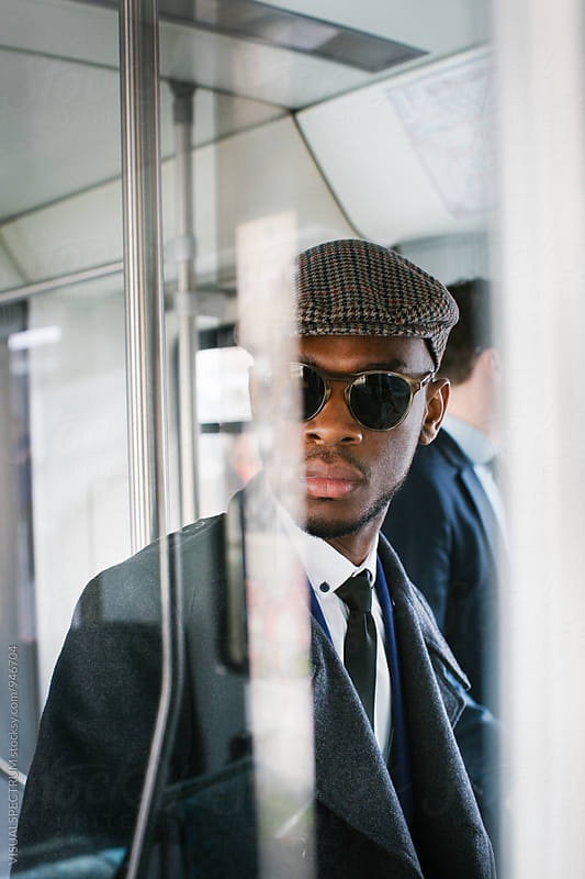 Portrait of Well-Dressed Young Black Businessman Standing in Train Car by Julien L. Balmer for Stocksy United