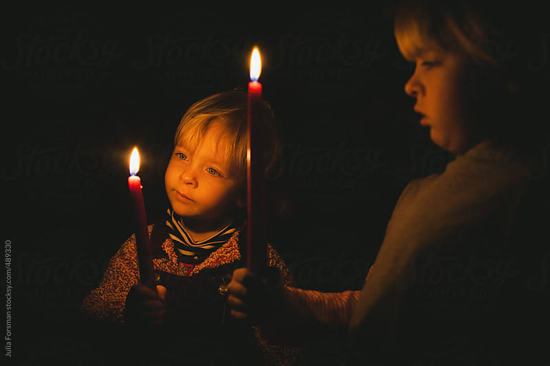 Two children with candles. by Julia Forsman for Stocksy United