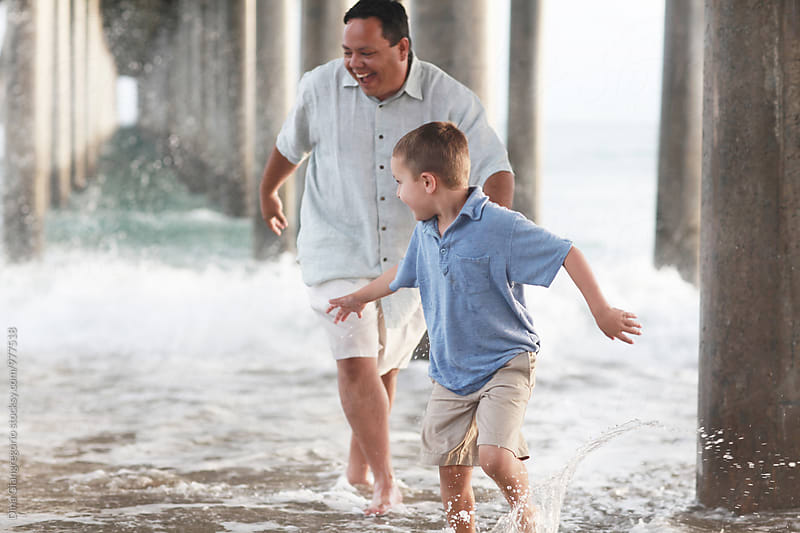 Father and Son Playing In Under The Pier In The Ocean by Dina Giangregorio for Stocksy United