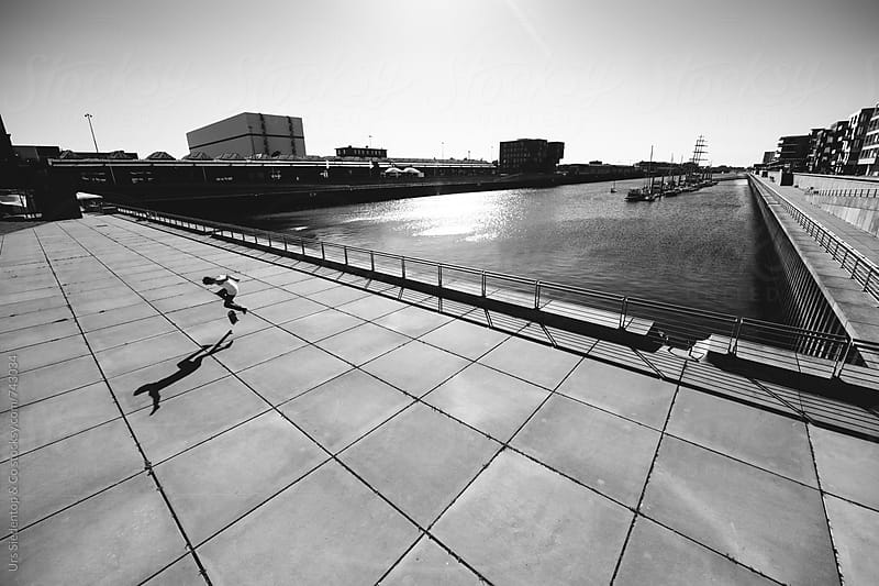 Skateboarding in modern harbor architecture by Urs Siedentop & Co for Stocksy United